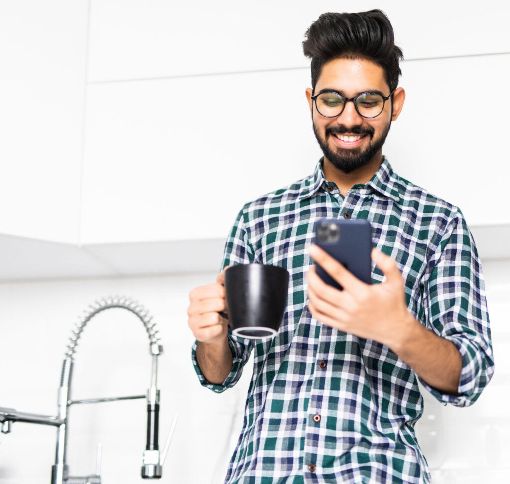 a man holding a cup of coffee and smiling while looking at his cell phone